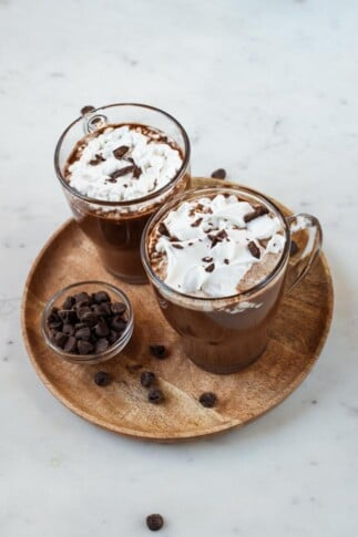 A picture of 2 glass jars with vegan hot chocolate topped with whipped cream and chopped dark chocolate