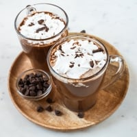 A square picture of 2 glass jars with vegan hot chocolate topped with whipped cream and chopped dark chocolate