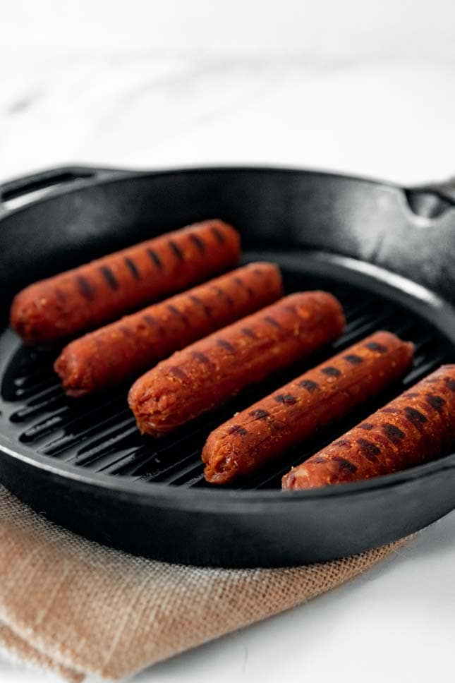 Photo of a skillet with some vegan sausages
