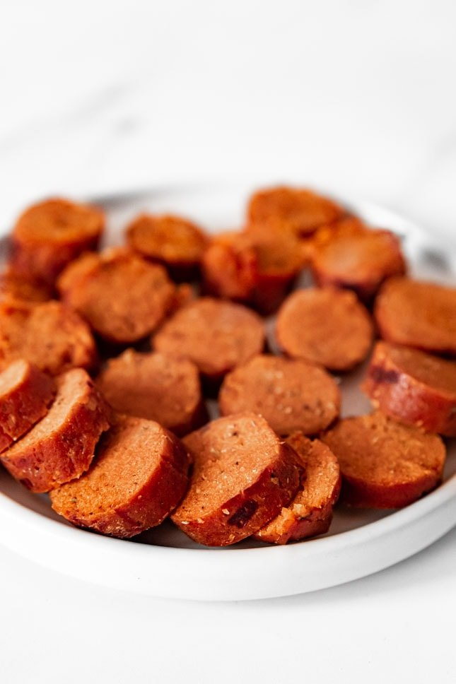 Photo of a plate with some vegan sausages cut in slices