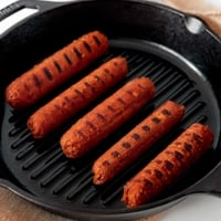 Square photo of some vegan sausages on a skillet