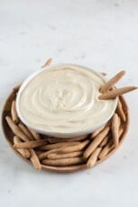 A picture of a bowl of homemade cashew cheese with bread sticks