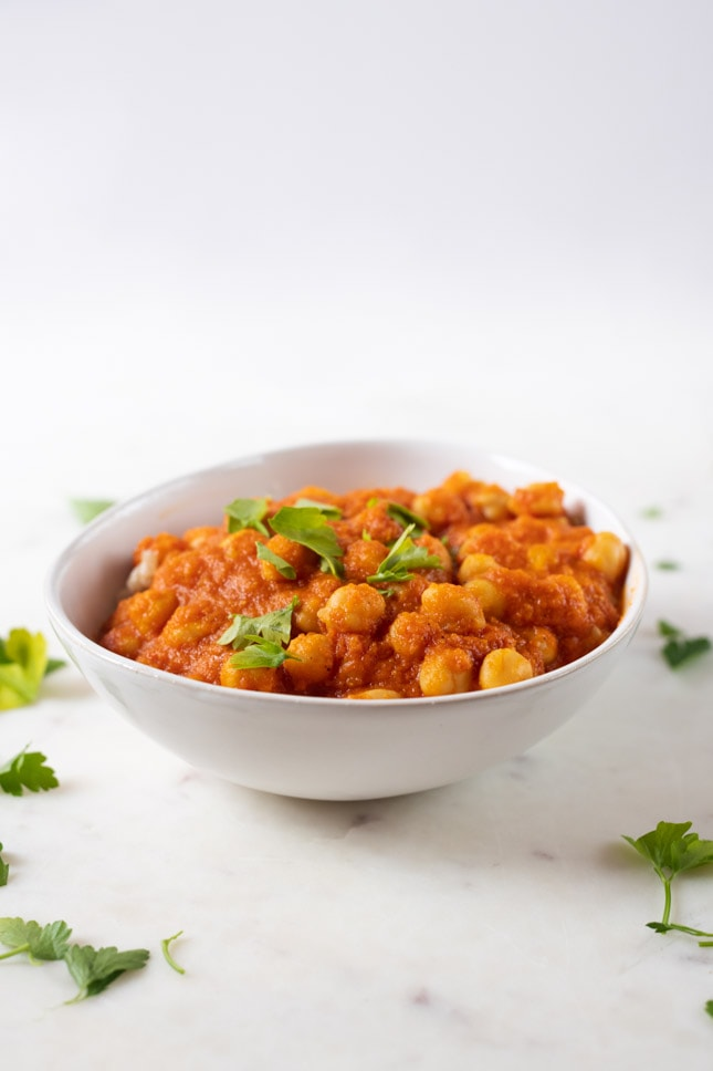 A side shot of a bowl with vegan chana masala with some parsley on top