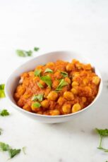 A picture of a white bowl with homemade chana masala topped with fresh parsley