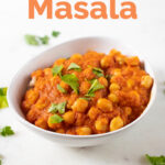 A picture of a white bowl with homemade chana masala topped with fresh parsley with the words chana masala