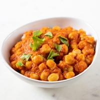 A square picture of a white bowl with homemade chana masala topped with fresh parsley