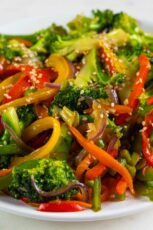 A close shot of a dish with veggie stir fry topped with sesame seeds