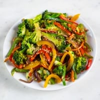 A square picture of a dish with veggie stir fry made from scratch