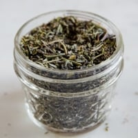 A square picture of a glass jar with homemade Italian seasoning
