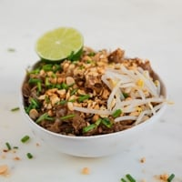 A square picture of a bowl of vegan pad Thai with a sliced lime on top