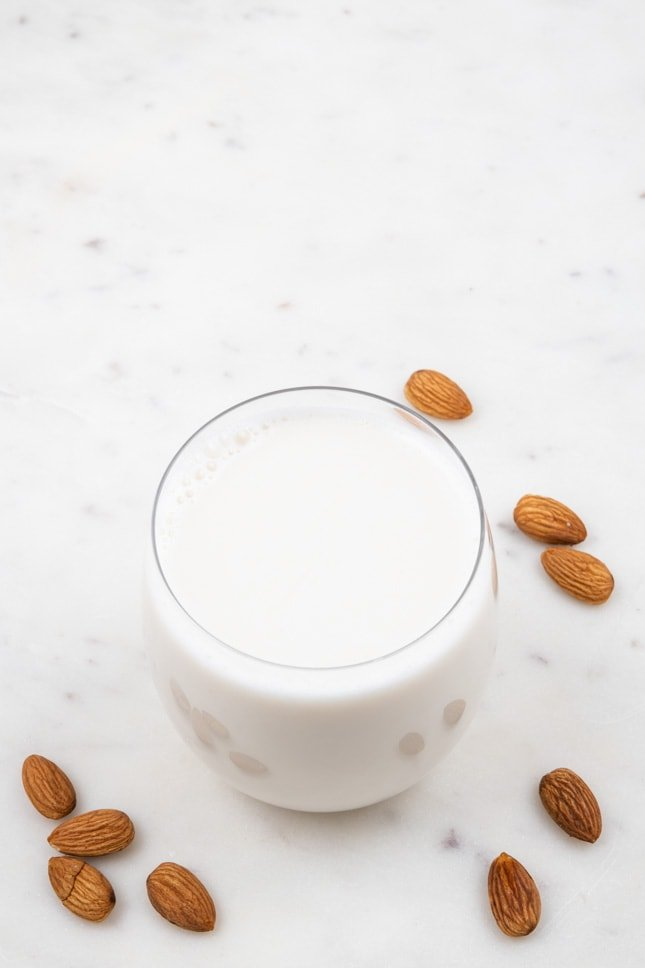Photo of a glass of almond milk sorrounded by some almonds