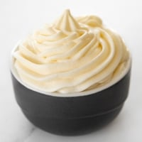 Square photo of a bowl of vegan cream cheese frosting