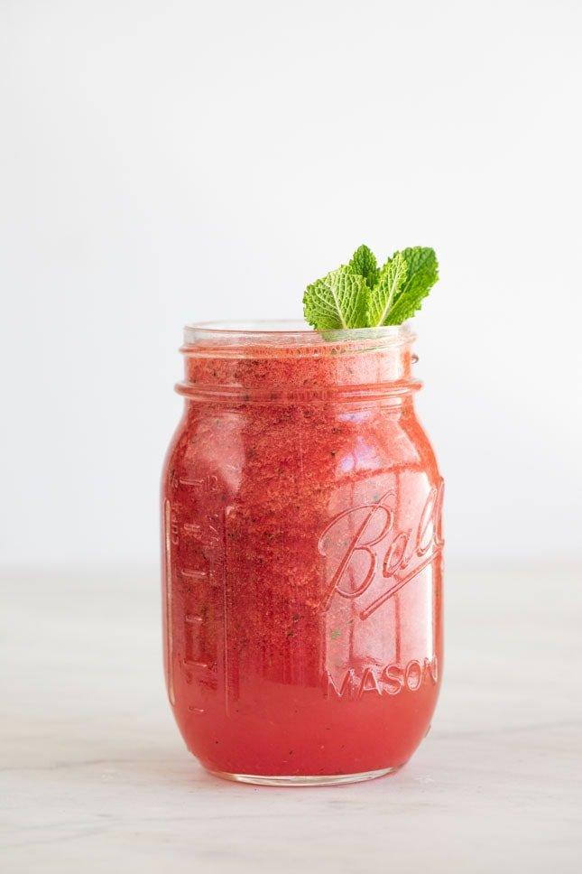 Side shot of a jar of watermelon smoothie decorated with mint leaves