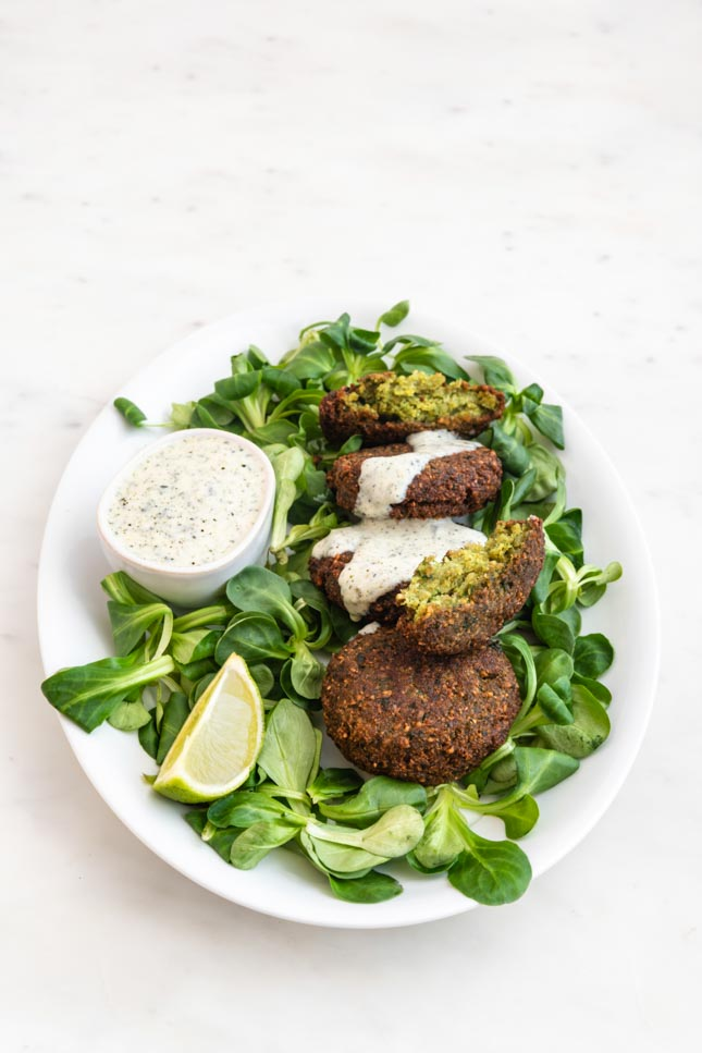 Photo of a plate of falafel, vegan yogurt sauce and some greens