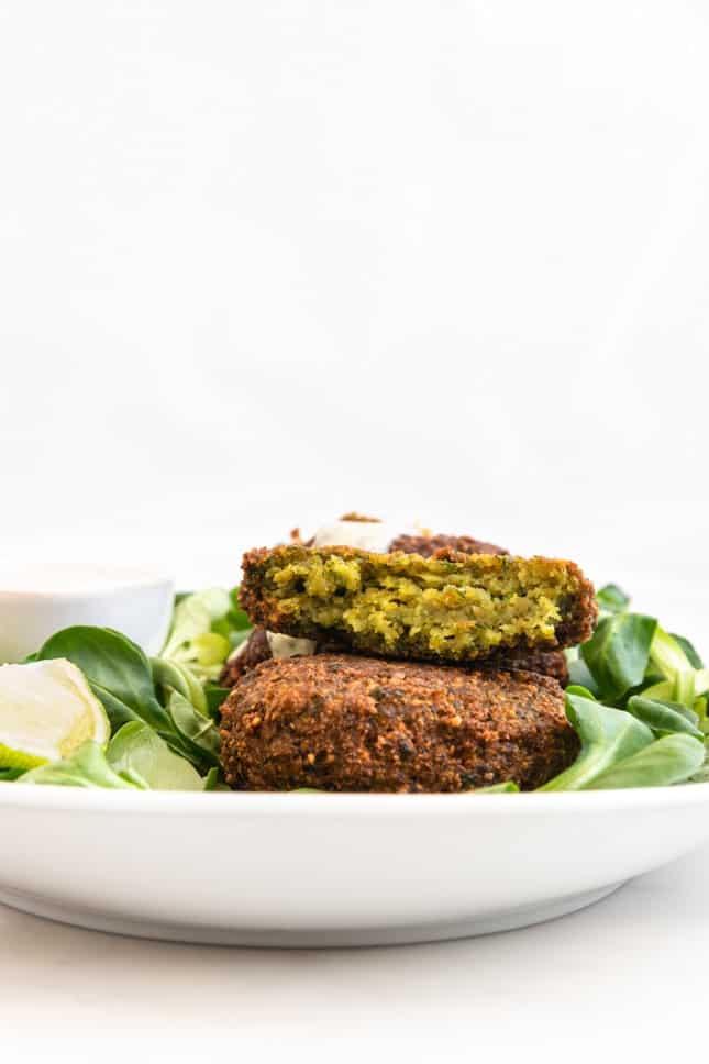 Side shot of a plate of falafel and vegan yogurt sauce