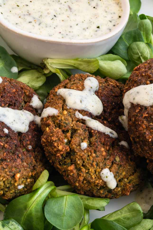 Close-up shot of a plate of falafel with some vegan yogurt sauce on top