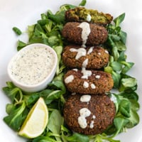 Square photo of a plate of falafel over some greens and vegan yogurt sauce on top