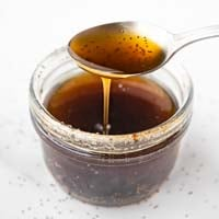 Square photo of a glass jar of poppy seed dressing