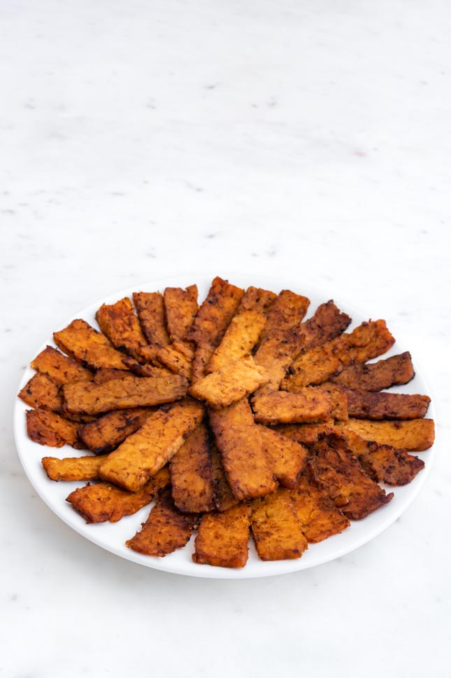 Photo of a plate with slices of tempeh bacon on it