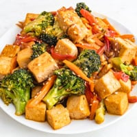 Square photo of a plate of tofu stir fry with sesame seeds on top