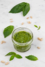 Photo of a glass of vegan pesto decorated with basil leaves and pine nuts