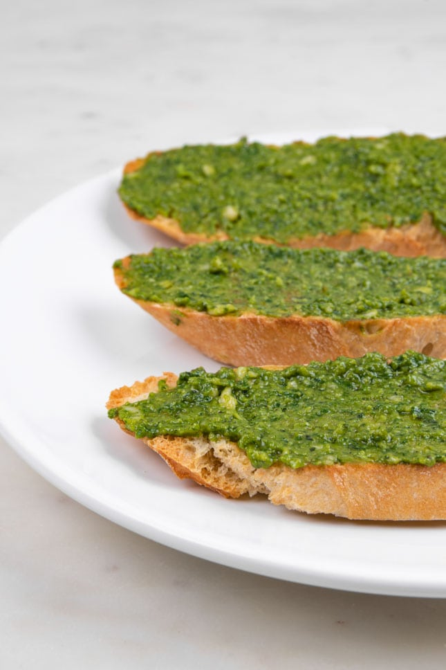 Photo of 3 slices of bread with some vegan pesto spread over them