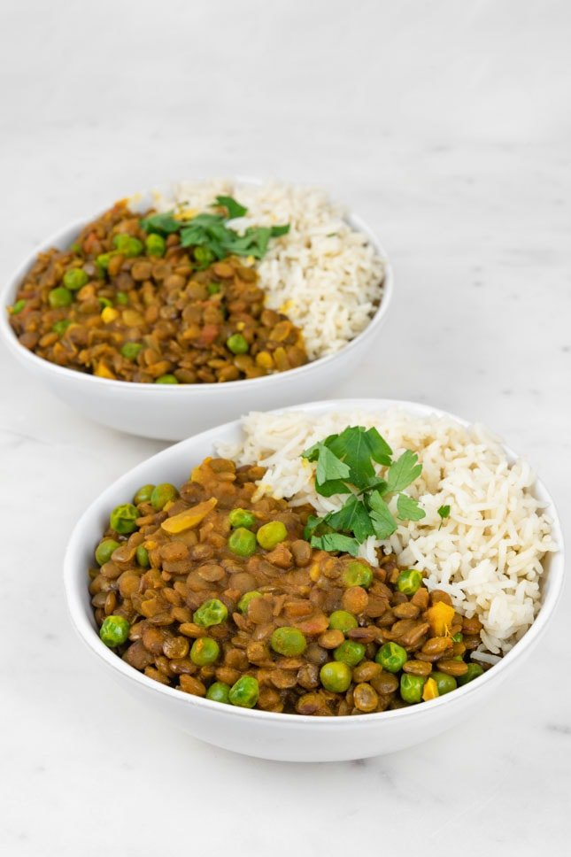 Photo of 2 bowls of lentil curry served with rice