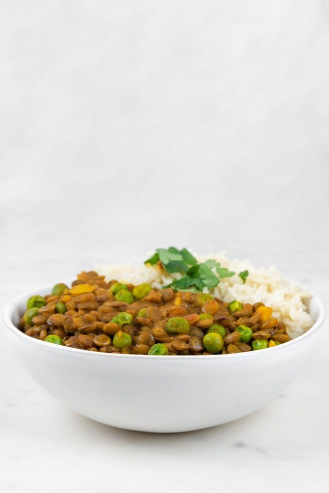 Side shot of a bowl of lentil curry with rice