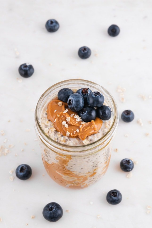 Photo of a glass jar of overnight oats decorated with some blueberries