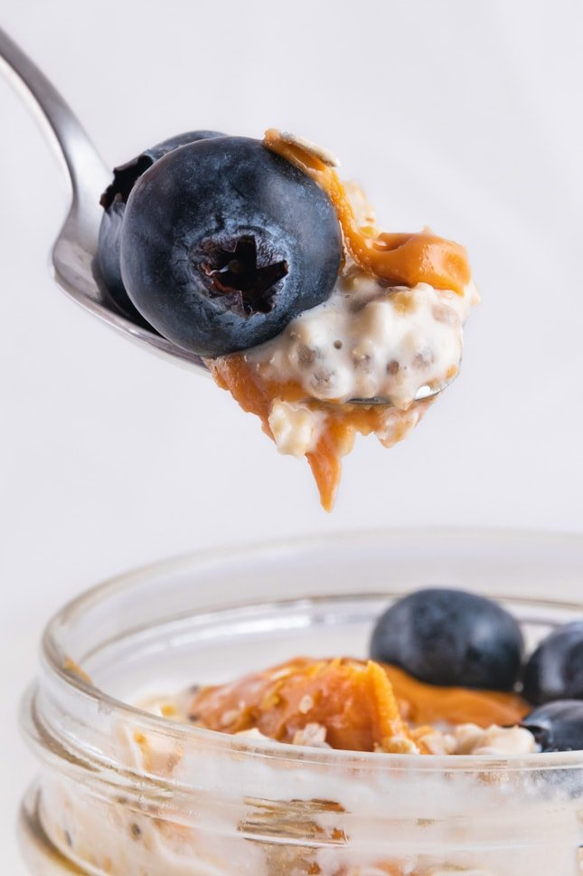 A spoonful of overnight oats and some blueberries