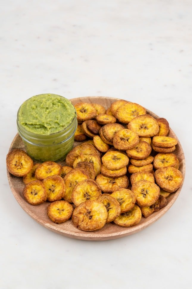 Photo of a plate of plantain chips with a little bowl of guacamole