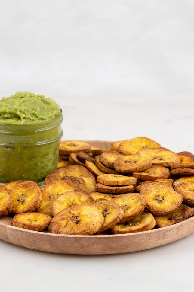 Side shot of a plate of plantain chips with guacamole