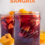 Side shot of a glass jar of sangria with the words how to make sangria