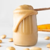 Square photo of a glass jar of creamy almond butter