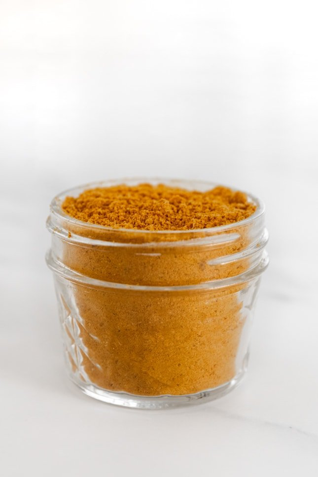 Side photo of a small glass jar of curry powder
