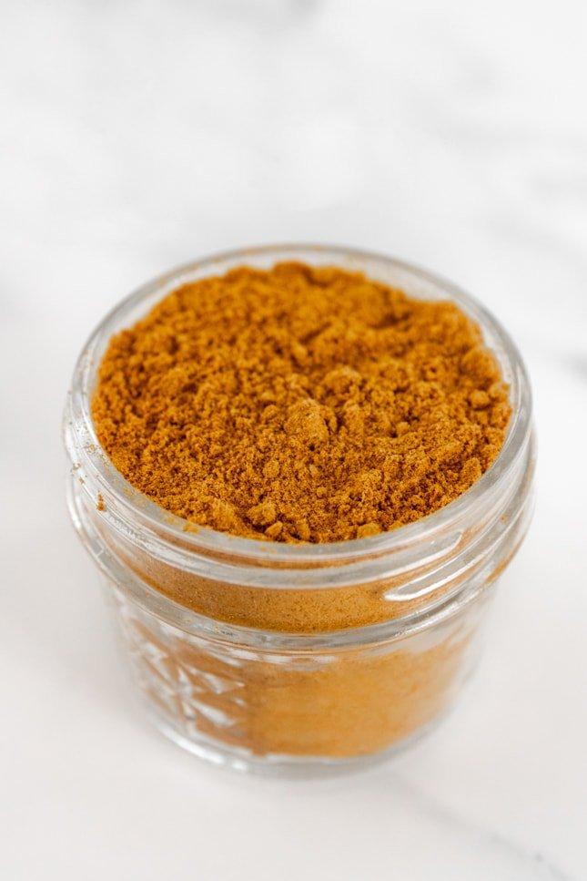 Photo of a small glass jar of curry powder