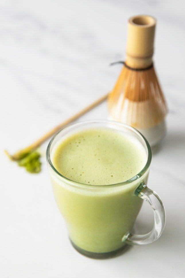 Photo of a cup of matcha latte with a bamboo whisk on the side