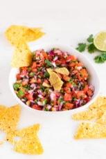 Photo of a bowl of homemade pico de gallo with some tortilla chips