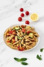Photo of a plate of vegan pasta salad decorated with tomatoes and some herbs