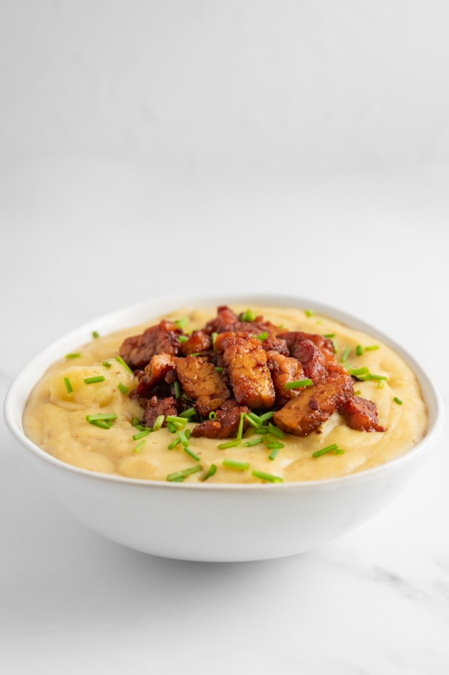 Photo of a bowl of vegan potato soup with tempeh bacon as a topping