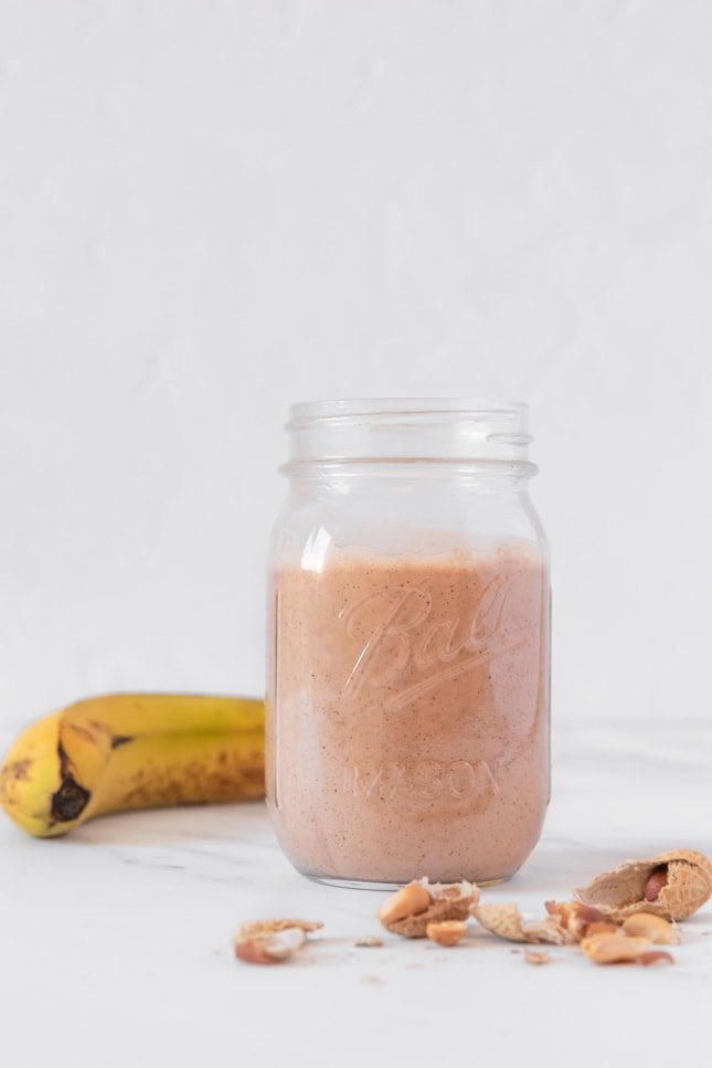 Side shot of a glass jar of vegan protein shake