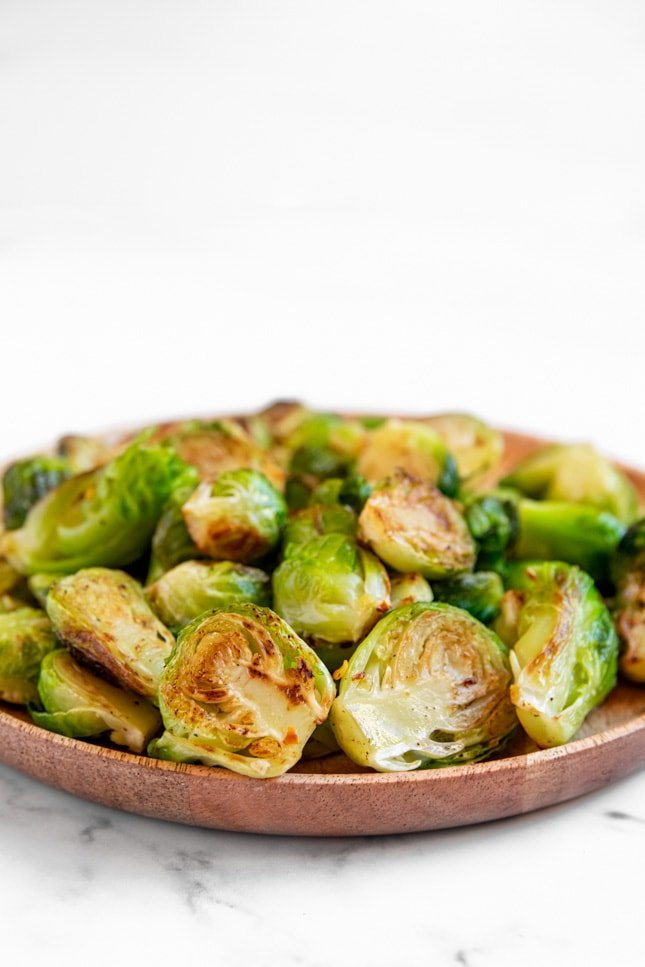 Side shot of a plate of sauteed Brussels sprouts
